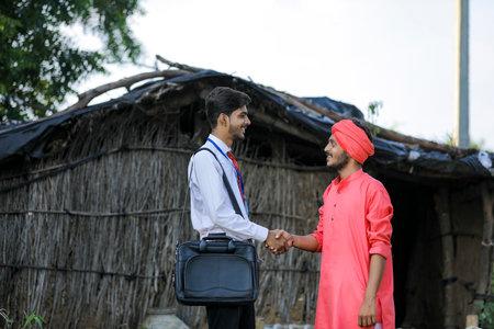 Young indian banker or agronomist visit poor farmer family Banque d'images