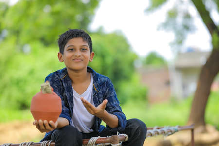 Cute indian child holding clay piggy bank in hand