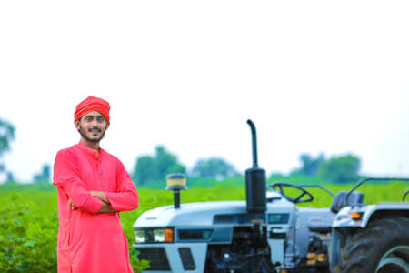 Technology and people concept, Portrait of young indian farmer with tractor