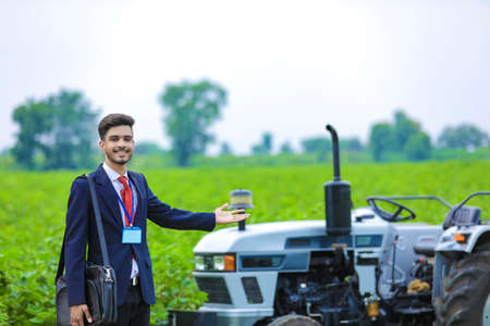 Young indian agronomist or bank officer with new tractor at agriculture field
