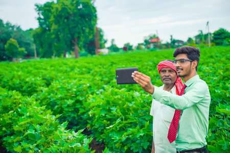Young indian agronomist taking selfie with farmer at field