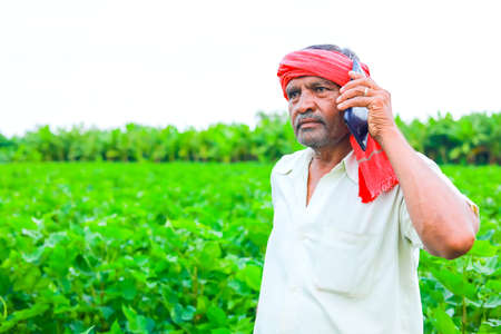 young indian farmer using smartphone at field