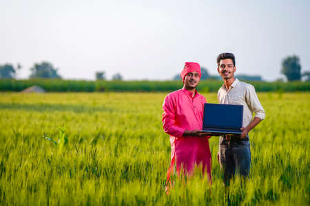 Young indian agronomist or banker showing laptop screen at green wheat field
