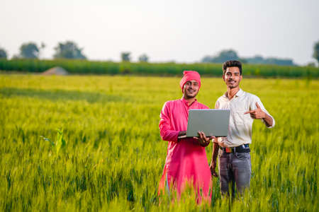 Young indian agronomist and farmer using laptop for seeing some information about farming
