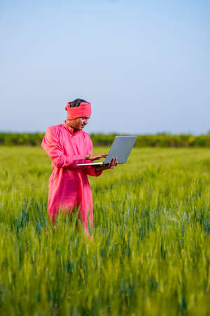 Young indian farmer using laptop at green wheat field