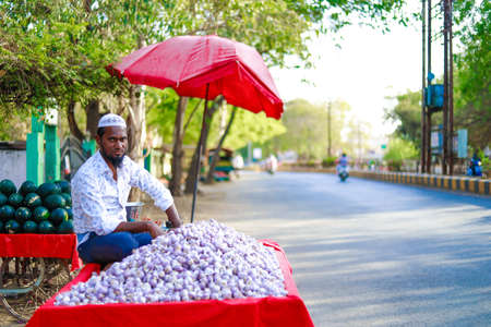 Indian man selling garlic on street side market
