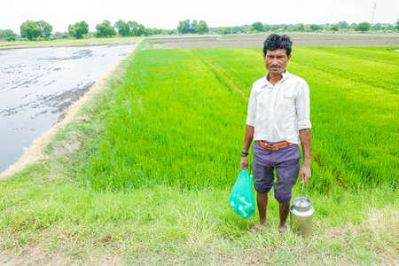 Young Indian man standing in rice field with holding Cary bag and steel box in hand