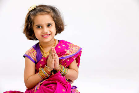 Cute indian little girl in traditional wear and praying on white background.