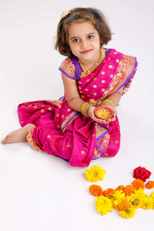 Cute indian little girl in traditional wear and holding oil lamp in hand on white background