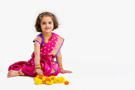 Cute indian little girl in traditional wear and showing expression on white background