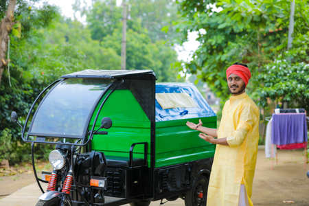 Young indian man standing with garbage van