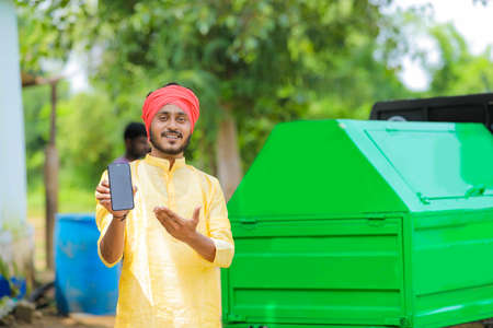 Young indian man showing smart phone screen with copy space Foto de archivo