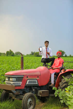 Young indian farmer and bank officer sitting on new tractor and officer showing mobile screen at agriculture field