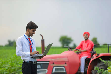 Farmer sitting on tractor and Young indian bank officer using laptop at agriculture field