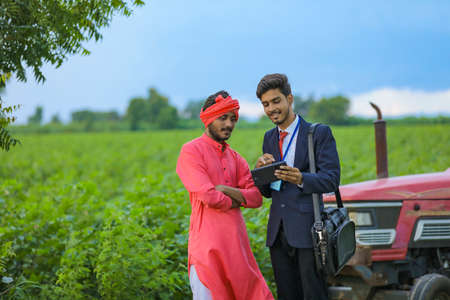 Young indian bank officer showing some information in smartphone to farmer at agriculture field