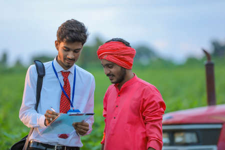 Young indian bank officer showing detail of loan paper to farmer at field