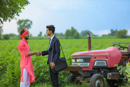 Young indian farmer welcome to bank officer at agriculture field