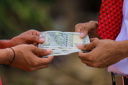 Young indian farmer receive money from banker at home