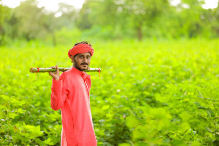 Young indian farmer in traditional wear and holding wooden stick in hand at field
