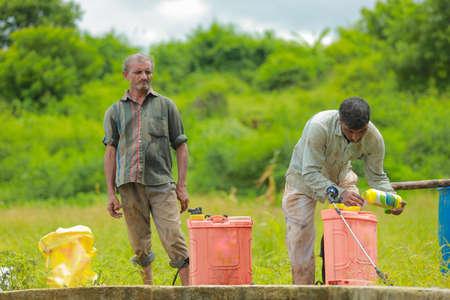 Indian labour liquid fertilizer mixing in bucket at field