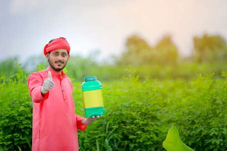 Young indian farmer showing fertilizer bottle at green field