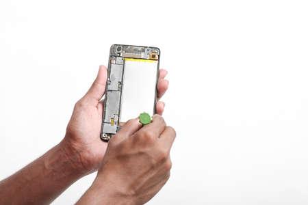 Repairman disassembling smartphone with screwdriver.
