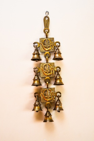 A brass metal wall hanging with three square shapes joined together  Each shape has an AUM  OM  along with Ganesha inscribed in it  There are two bells hanging from the sides of each square piece  Stock Photo - 19178634