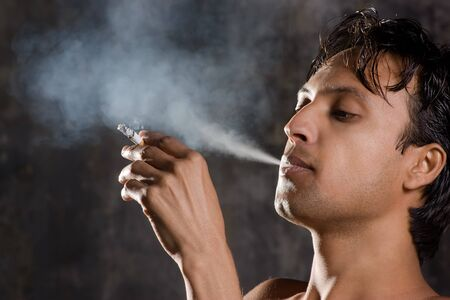 Close-up of an intensively smoking man with heavy smoke