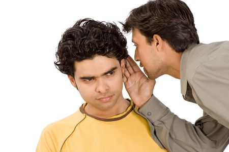 Close-up of a man whispering confidentially into the ear of another man, both with serious expressions.