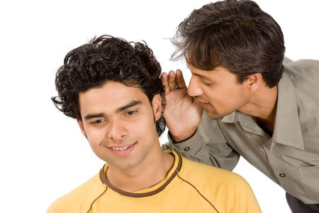 Close-up of a man whispering confidentially into the ear of another man, both with happiness expressions. Stock Photo