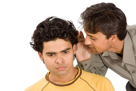 conspire: Close-up of a man whispering confidentially into the ear of another man, both with serious expressions.