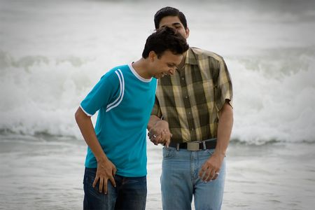 Two men standing on a beach at the shoreline, chatting and watching something