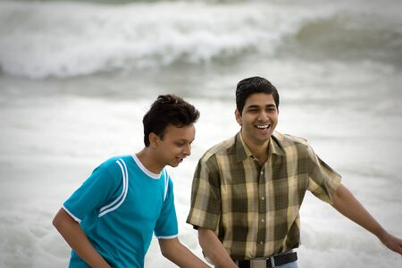 gay couple: Two men standing on a beach at the shoreline, chatting and watching something