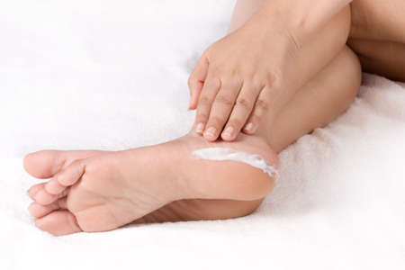 Woman applying cream to feet sitting over white towel