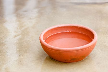 Clay red bowl filled with water and its reflection in water on floor   Stock Photo