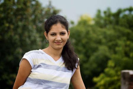 indianin: PiÄ™kne Indian uÅ›miecha siÄ™ dziewczynka uczucie chÅ'odnego powietrza i oddychania na zielone tÅ'o drzewa i niebo. Zdjęcie Seryjne