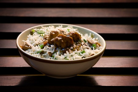 Risotto of rice and mushrooms in a bowl resting on wooden background photo