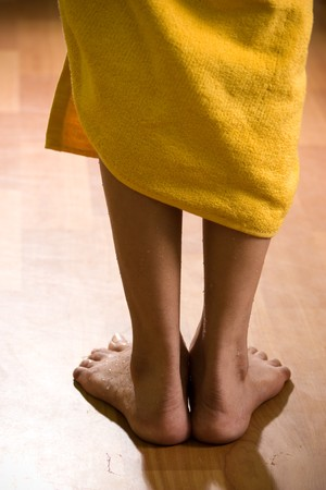 Beautiful and wet female legs at standing position on wooden floor, coming from bathroom.