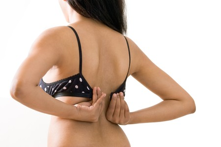 An Indian Girl dressing or undressing black bra, back view, showing her back, isolated on white photo