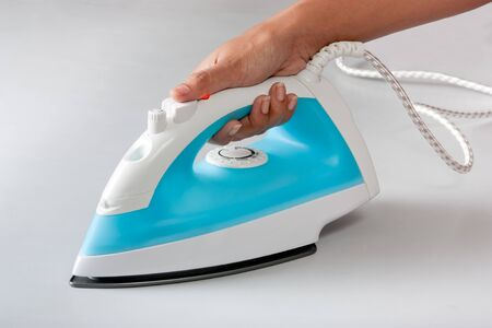 White blue electric steam iron in hand on a white background photo