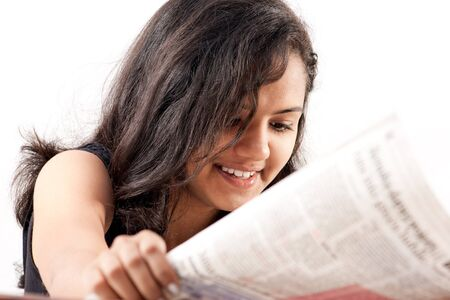 pretty indian  woman reading the newspaper and smilling