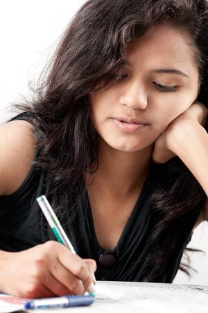 Beautiful indian girl is writing a test and thinking photo