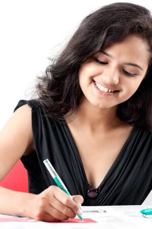 Beautiful indian girl is writing a test and smiling Stock Photo - 8550170