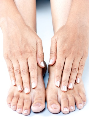 Beautiful feet and hand of a female isolated over white photo