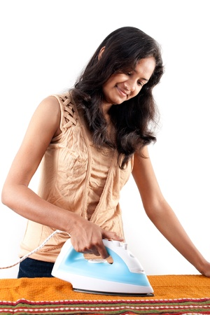 Indian girl looking,  smiling and doing press with electric steam iron photo