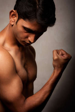 Portrait of young Indian angry man over dark background photo