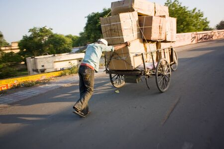 Typical Indian street scene man carrying carton box on hand wooden cart at road on height Editorial