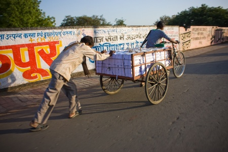 cart road: Typical Indian street scene man carrying books on rickshaw cart at road on height