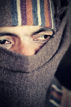 Close-up of an covered face by scarf  of Indian farmer. Grains and textures are added for some old and grunge effect. photo