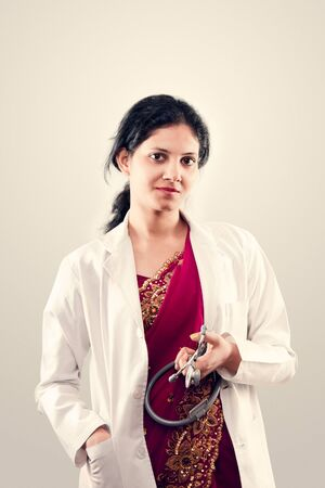 Indian beautiful Friendly lady doctor with stethoscope in sari Stock Photo